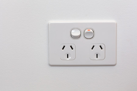 Modern Australia double power outlet on white wall Archivio Fotografico - 103353296