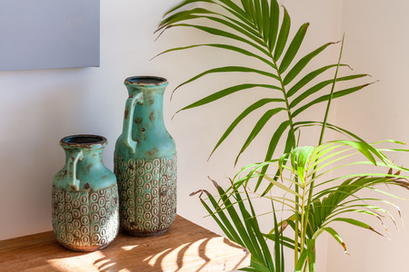 Two decorative vases on wooden table and Majesty Palm in sunlight - cozy home scene