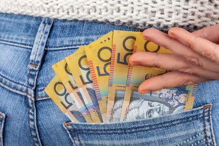Female hand reaching for 50 Australian dollar bills in her jeans back pocket 版權商用圖片