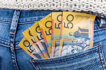50 AUD bills in fan shape placed in female jeans back pocket closeup - minimum wage concept