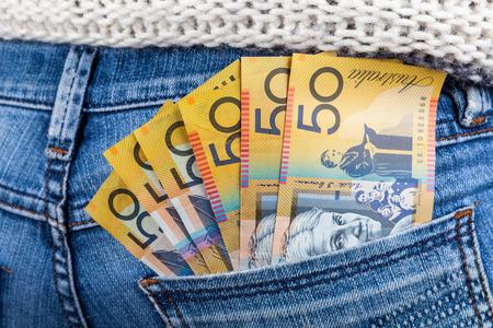 50 AUD factures en forme de ventilateur placé dans la poche arrière jeans femme gros plan - concept de salaire minimum