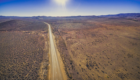 Rural road passing through dry land with scarce vegetation on bright sunny day - aerial panorama 写真素材