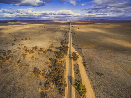 Straight rural road passing through plains of South Australia with clouds casting beautiful shadows on the land - aerial view