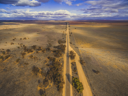 Straight rural road passing through plains of South Australia with clouds casting beautiful shadows on the land - aerial landscape Stok Fotoğraf