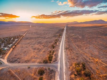 Rural highway leading into Ikara-Flinders Ranges national park at sunset - aerial view