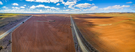 Wide aerial panorama of agricultural fields under beautiful blue sky with white fluffy clouds Stok Fotoğraf