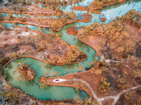 Small red car at the end of dirt road on the edge of beautiful river among gum trees in Australia - aerial view