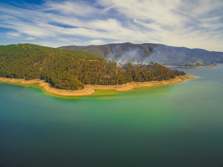 Aerial view of forest fire on shores of Blowering reservoir lake