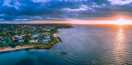 Sunset over ocean near coastline aerial panoramic landscape