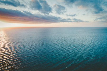 Lonely boat sailing calm ocean waters at sunset - aerial view