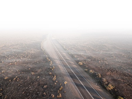 Rural highway passing through desert and disappearing in white clouds and haze