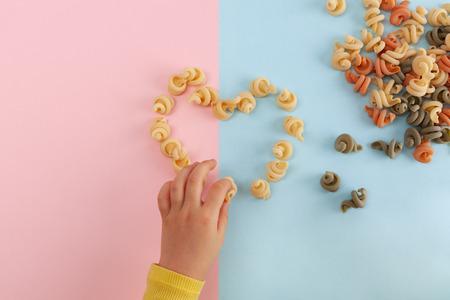 Girl's hand making heart shape from pasta shells