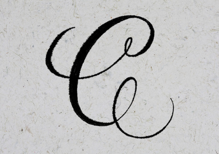 Letter C hand lettering with ink on textured kraft paper