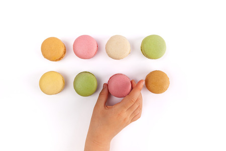 Girl's hand taking pink French macaron from two rows of colorful macarons isolated on white