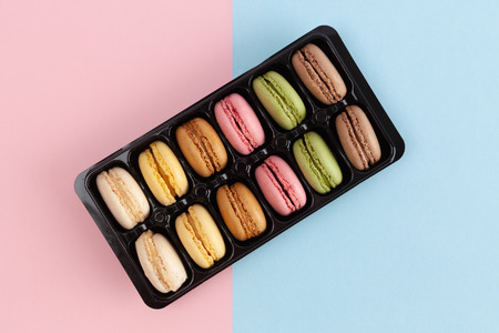 Top view of colorful French macarons in package on pink-blue background