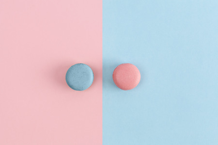 Pink and blue macarons on divided background. Clean design top view with copy space