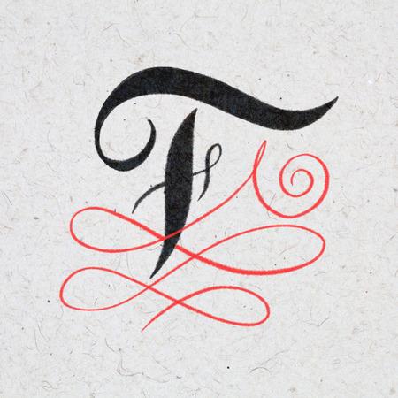 Calligraphic letter F with flourishes on kraft paper Standard-Bild - 117627595