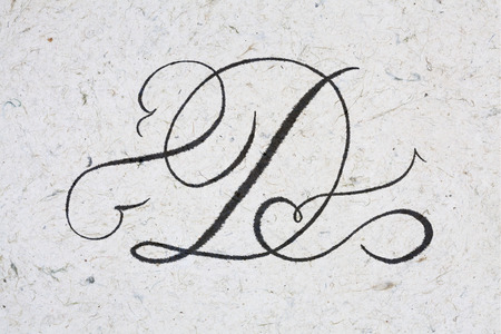 Calligraphy letter D - ink bleeding on kraft paper Standard-Bild
