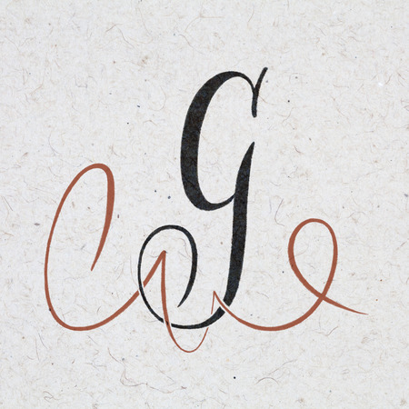Calligraphic letter G with flourishes on kraft paper Standard-Bild - 117627613