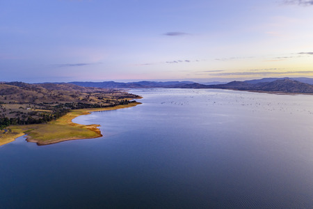 Beautiful rolling hills on Lake Hume coastline at twilight with copy space 写真素材