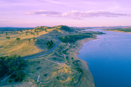 Scenic river and countryside road at sunset - aerial view 写真素材
