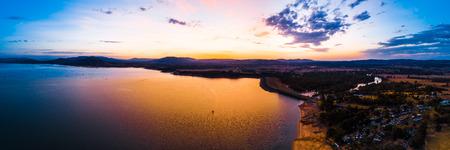 Lonely boat sailing across scenic lake at vivid orange sunset - aerial panorama 写真素材