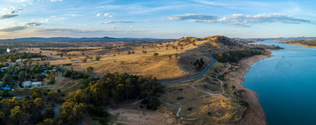 Scenic river and countryside rolling hills at sunset in Australia - aerial panorama