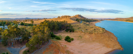 Aerial panorama of Lake Hume and yellow rolling hills at sunset. New South Wales, Australia