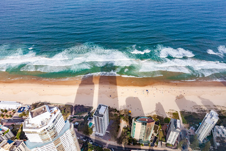 Long shadows on the beach from skyscrapers with people bathing - birds eye view. Gold Coast, QLD, Australia 写真素材