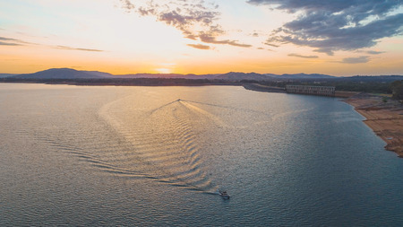 Aerial view of two boats sailing across lake in opposite directions at sunset in Australia
