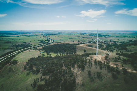 Wind turbines and rural highway in scenic countryside - aerial view