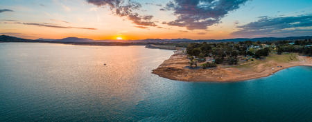 Wide aerial panorama of a tiny boat in big lake at sunset with copy space