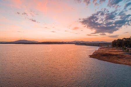 Aerial view of scenic lake in the beautiful orange glow of twilight time 写真素材