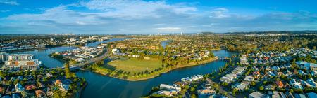 Aerial panorama of Varsity Lakes suburb, Reedy Creek and Lake Orr at sunset. Gold Coast, Queensland, Australia