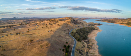 Aerial view of rolling landscape and river at sunset in Australia