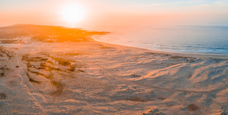 Aerial panorama of sunrise over ocean coastline with copy space