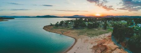 Sun disappearing behind mountains near Lake Hume Village - aerial panorama