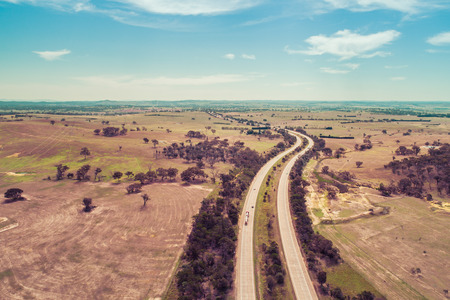 Aerial landscape of Hume Highway passing through agricultural land. Cullerin, New South Wales, Australia