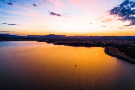 Lone boat sailing across scenic lake at vivid orange sunset - aerial view 写真素材