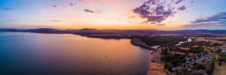 Lonely boat sailing across scenic lake at vivid orange sunset - aerial panoramic landscape