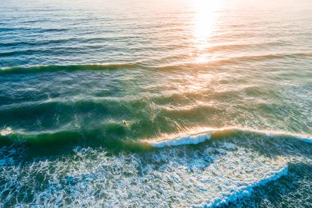 Vista aérea de serfer en el vasto océano al atardecer