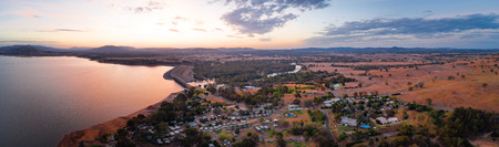 Wide aerial panorama of Lake Hume Village and Murray River surrounded by scenic countryside and hills at dusk 写真素材