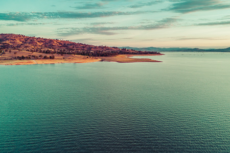 Yellow rolling hill and lake coastline at sunset - aerial view 写真素材