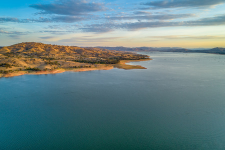 Calm lake and rolling yellow hills at sunset - aerial view
