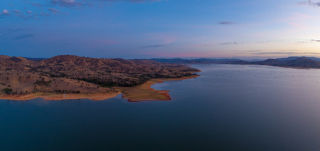 Rolling hills on Lake Hume coastline at twilight - aerial panorama with copy space 写真素材