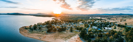Sun touching the horizon over mountains and Lake Hume Village - wide aerial panorama