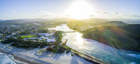 Aerial panorama of sunset with sun flare over Tallebudgera creek in Gold Coast, Queensland, Australia
