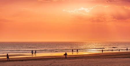 People enjoying summer evening on ocean shore at sunset in Australia