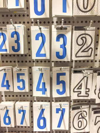 Self adhesive vinyl numbers for mailboxes hanging in hardware store Фото со стока