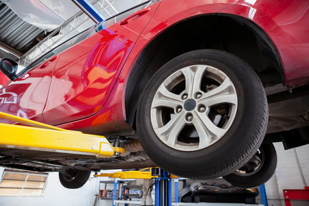 Red car lifted on hydraulic car lift in a workshop during routine service